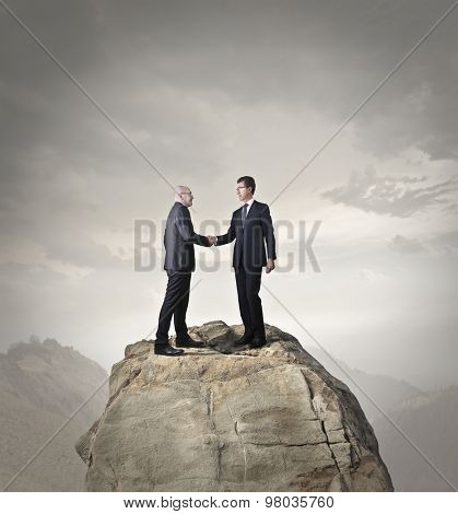 Businessmen on top of a rock