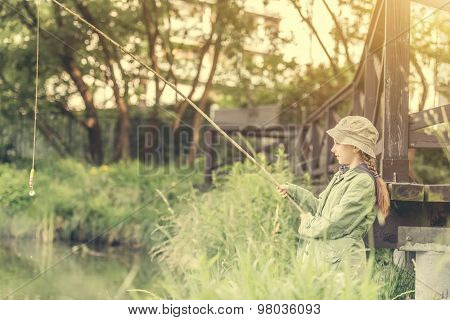 little fisher girl holdin a rod at a river near a bridge