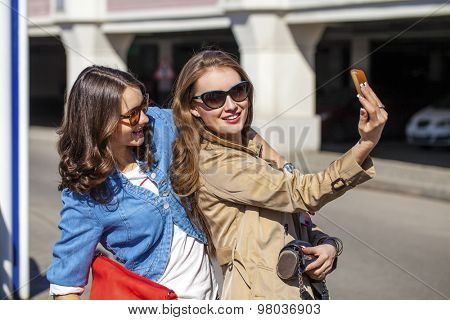 Two Happy Girlfriends Taking Self Portrait with Their Phone Camera Outdoors