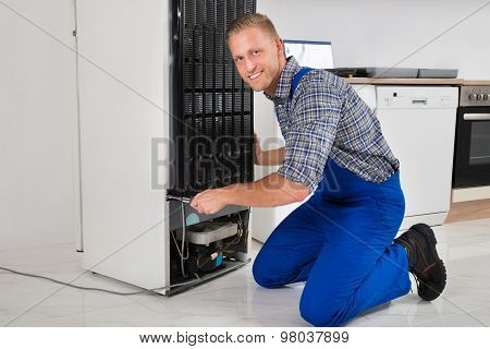 Worker Repairing Refrigerator In House