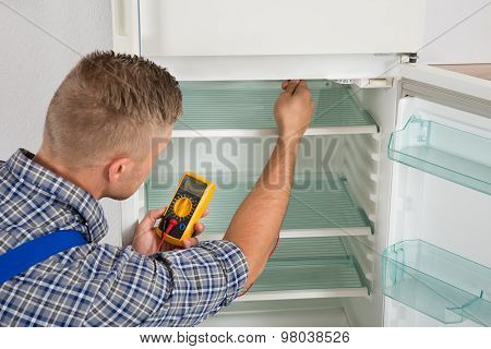 Technician Checking Fridge With Multimeter