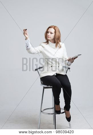 young woman with pen and tablet writes or shows on grey background