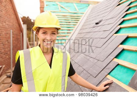 Female Construction Worker On Site Laying Slate Tiles