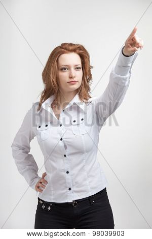 Young businesswoman in white shirt pointing index finger