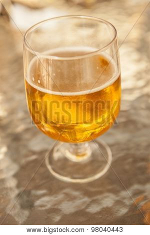 Misted glass of beer on a glass table in a bar.