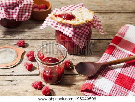 handmade raspberry jam in jars with kitchen spoon and towel on rustic table