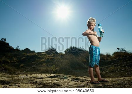 Boy Standing In The Sand Holding A Water Bottle Showing Muscle
