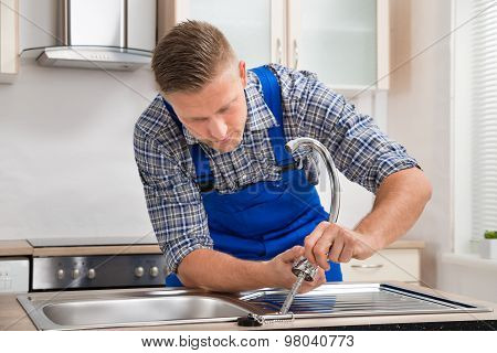 Repairman Installing Faucet Of Kitchen Sink