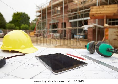 Close Up Of Plans And Digital Tablet On Building Site