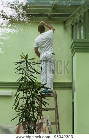 A man standing on a ladder and painting walls in green, shot through a window