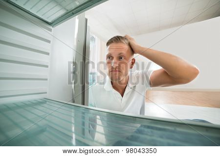 Man Looking In Empty Refrigerator