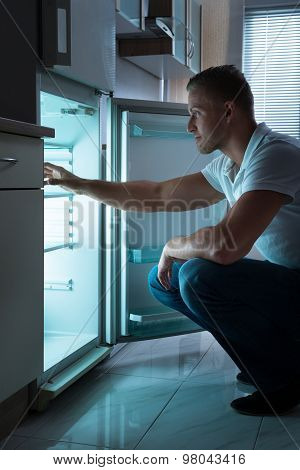Man Sitting In Front Of Empty Fridge