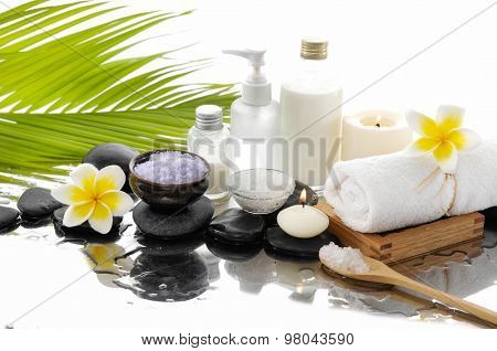 Spa set with salt in spoon, towel, candle ,oil, ,stones –green palm background