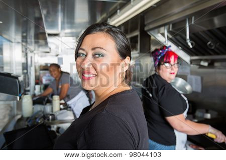 Three Busy Workers Inside  A Food Truck