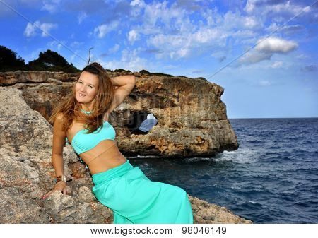Young Attractive Woman On Cyan Glamour Dress Leaning On Rock Cliff At Spain Coast