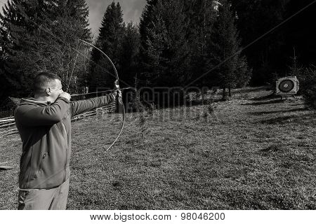 A man shoots a bow. Man engaged in archery.