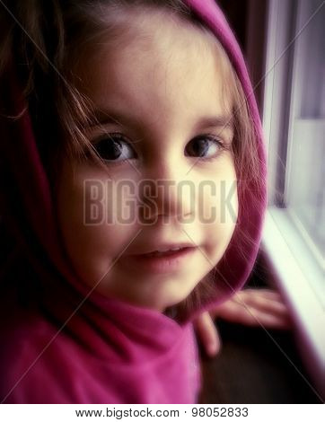 Authentic close up of a little girl looking at camera by window - soft focus - Instagram style filter