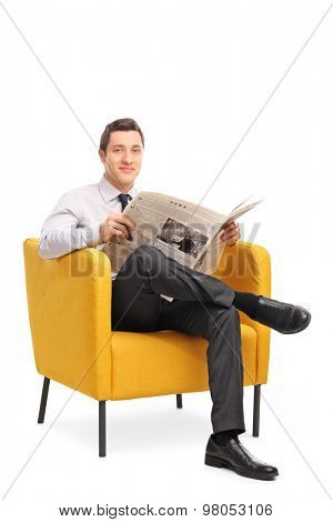Vertical shot of a young guy sitting in an armchair and holding a newspaper isolated on white background