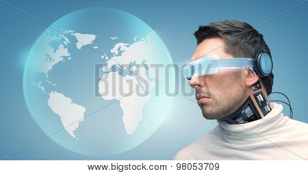 people, technology, future and progress - man with futuristic glasses and microchip implant or sensors over blue background and earth globe hologram