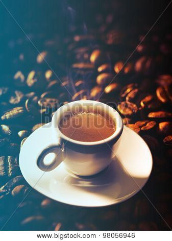 Cup of coffee on a beautiful beans background.Filtered image: cool cross processed vintage effect.
