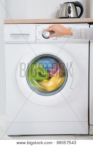 Person Hands Turning Button Of Washing Machine
