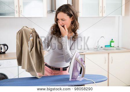 Woman Looking At Iron Burned Cloth