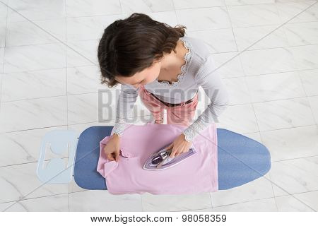 Woman Ironing Cloth On Ironing Board