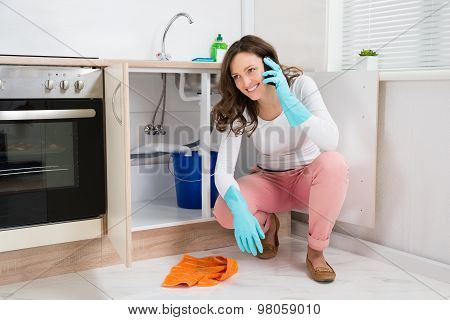 Woman Wiping While Talking On Mobile Phone