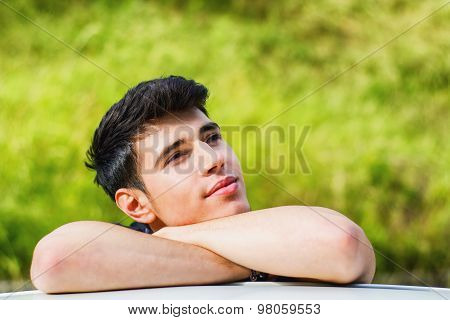 Young man looking at camera outdoor, leaning with head resting on hands
