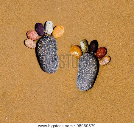 Foots shape by stone in sand