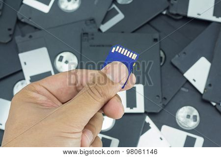 Hand Holding Sd Card With Floppy Disk Background