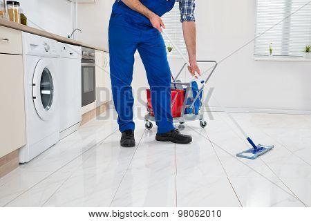 Worker Cleaning Floor In Kitchen Room