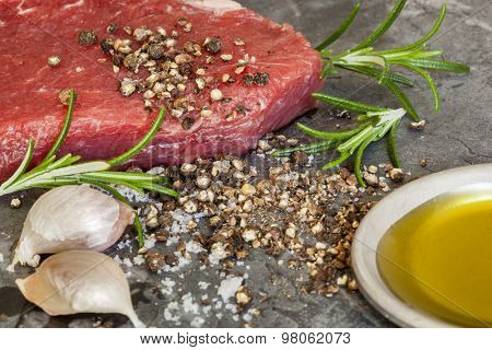 Raw beef steak with peppercorns, rosemary, garlic cloves and olive oil.