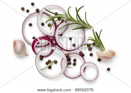 Food background of onion rings, peppercorns, rosemary and garlic cloves, isolated on white.  Overhead view.