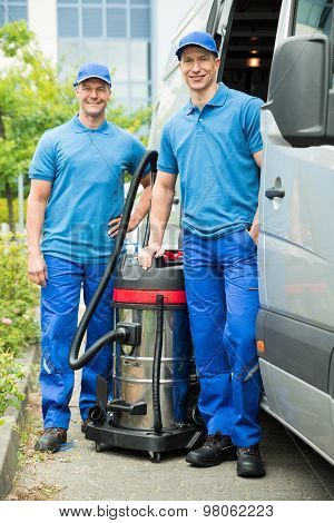 Two Male Cleaners With Vacuum Cleaner