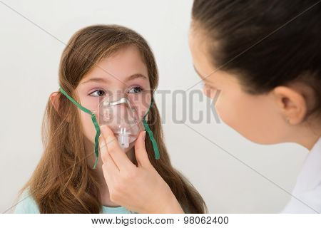 Doctor Holding Inhaler Mask For Girl Breathing