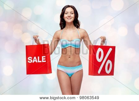 people, fashion, swimwear, summer sale and beach concept - happy young woman in bikini swimsuit with red shopping bags over blue holidays lights background