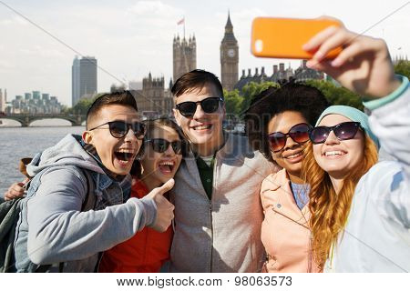 tourism, travel, people, leisure and technology concept - group of smiling teenage friends taking selfie with smartphone over houses of parliament and thames river in london background
