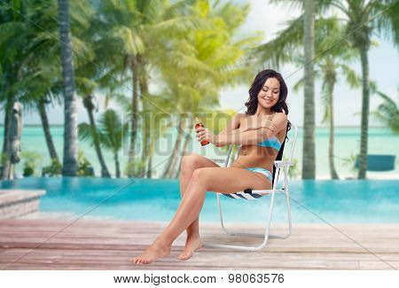 people, tanning, skincare, summer and beach concept - happy young woman in bikini swimsuit sunbathing on folding chair and applying sunscreen to her skin over tropical beach at hotel resort background