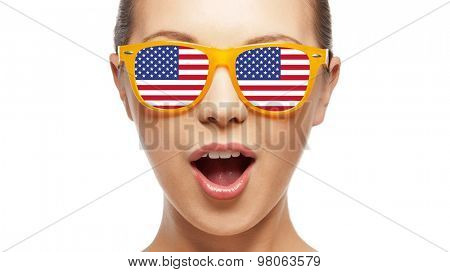 people, patriotism, national pride and independence day concept - happy teenage girl in sunglasses with american flag