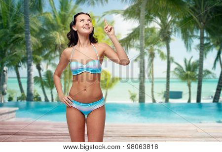 people, travel, swimwear and summer concept - happy young woman in bikini swimsuit pointing finger up to something imaginary over tropical beach with palm trees and pool at hotel resort background