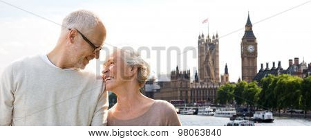 family, age, tourism, travel and people concept - happy senior couple over houses of parliament and big ben clock tower in london