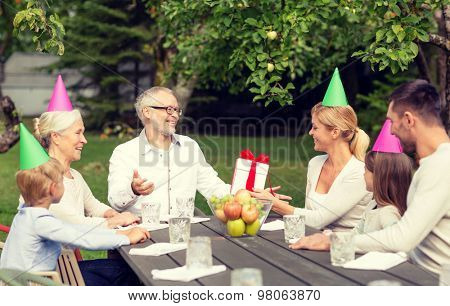 family, happiness, generation, home and people concept - happy family with gift box having holiday dinner outdoors