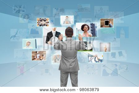 business, people, communication, technology and connection concept - businessman working with images on virtual screen over blue background from back