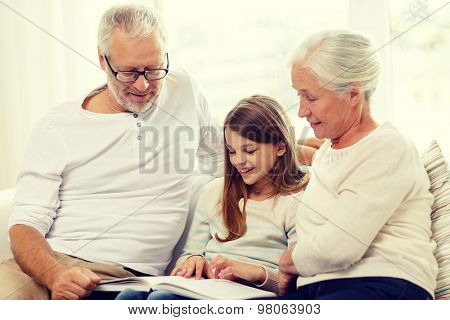 family, generation and people concept - smiling grandfather, granddaughter and grandmother with book sitting on couch at home