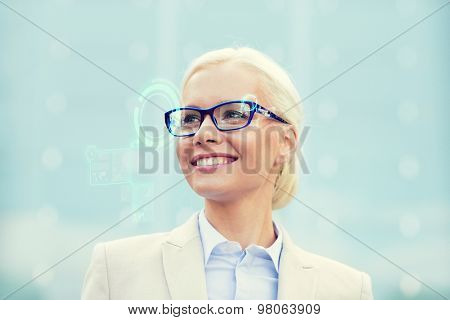 business, people, technology and education concept - young smiling businesswoman in eyeglasses with virtual screens hologram outdoors