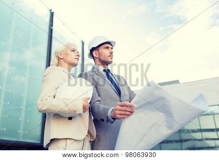 business, partnership, architecture and people concept - businessman and businesswoman with blueprint and helmets on city street