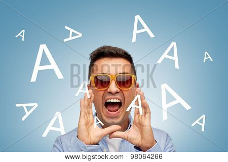 summer, emotions, communication and people concept - face of angry middle aged latin man in shirt and sunglasses over blue background with a letters