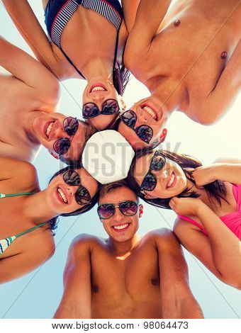 friendship, happiness, summer vacation, holidays and people concept - group of smiling friends wearing swimwear standing in circle with volleyball over blue sky