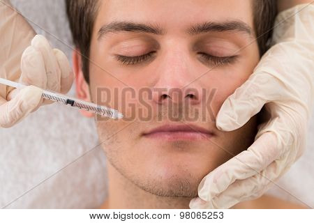 Doctor Giving Injection On Face Of Man